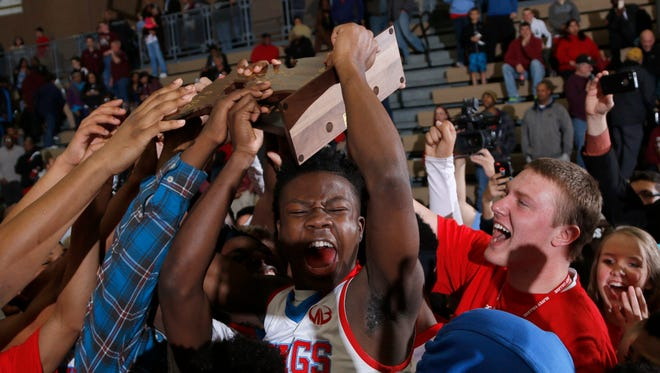 Lansing Everett fans celebrate with players, including Nyrell Powell, center, after a 91-78 win over Kalamazoo Central.