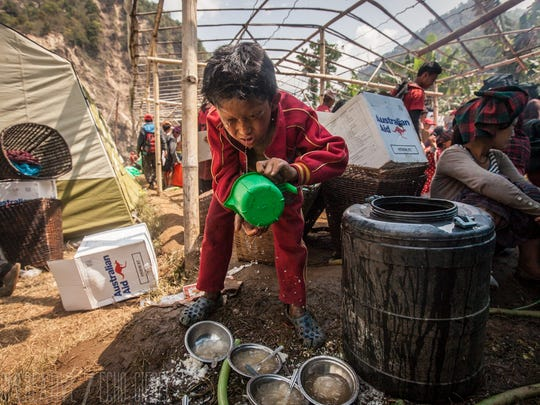A child splashes water on his face in the village of Baluwa in the Gorkha district of Nepal. Cody Tuttle, a Kimball Township native, is assisting in the relief efforts following to earthquakes.