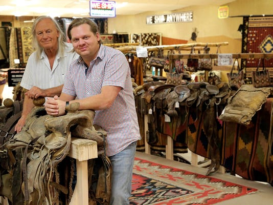 Dusty Henson, owner and founder of El Paso Saddleblanket and Luc Henson Wells, president, stand by some of the used saddles they sell at the store and online. Henson announced Friday that he will close down the retail store located at 6926 Gateway Blvd. east and move his operation to the stores' online sales.