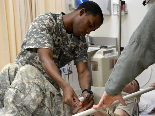Spc. Leroy Offord of Monroe, a medic from Headquarters and Headquarters Company, 528th Engineering Battalion, checks the heart rate of a patient he received during rotation training in the emergency room.