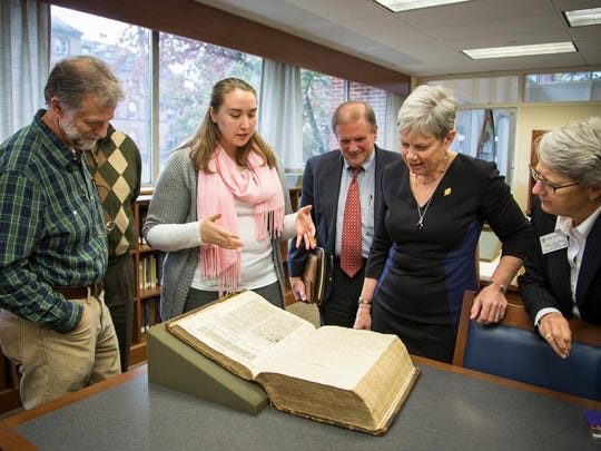 "Library worker Cassie Brand explains the authentication process to President MaryAnn Baenninger and other administrators after graduate student Brian Shetler found this rare first-edition 1611 King James ""He"" Bible in a stored in a box while working at the Drew University Library."