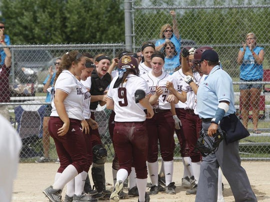 Ankeny's Olivia Brooks is greeted at home plate by her teammates after hitting a three-run homer during the Hawkettes' 9-0 victory over Linn-Mar (Marion) in the seventh-place game of the Class 5-A state softball tournament.