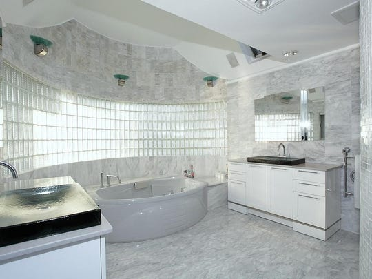 The master bath is all marble, with an enormous sunken tub and glass shower.