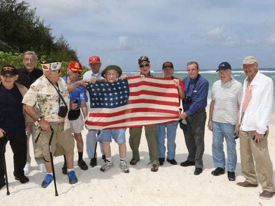 World War II veteran Frank Pontisso of Des Moines, 90, second from left is shown among a group of fellow veterans on the landing beaches at Guam during his 2015 return trip to the region and the island of Iwo Jima where he fought 70 years ago.