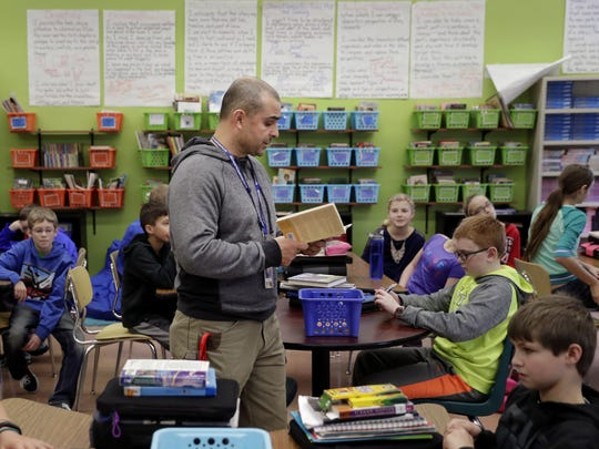 "Ken Wertman, a substitute teacher, reads a passage from ""The Breadwinner"" to a sixth-grade language arts class on Tuesday at Horace Mann Middle School in Neenah."