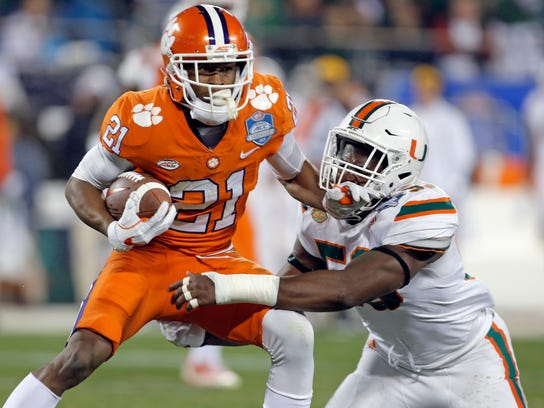 Clemson's Ray-Ray McCloud (21) is tackled by Miami's Zach McCloud (53) during the first half of the Atlantic Coast Conference championship NCAA college football game in Charlotte, N.C., Saturday, Dec. 2, 2017. (AP Photo/Bob Leverone)