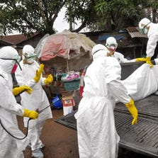 Health workers carry load the body of a woman that they suspect died from the Ebola virus, onto a truck in front of a makeshift shop in an area known as Clara Town in Monrovia, Liberia, Wednesday, Sept. 10, 2014.