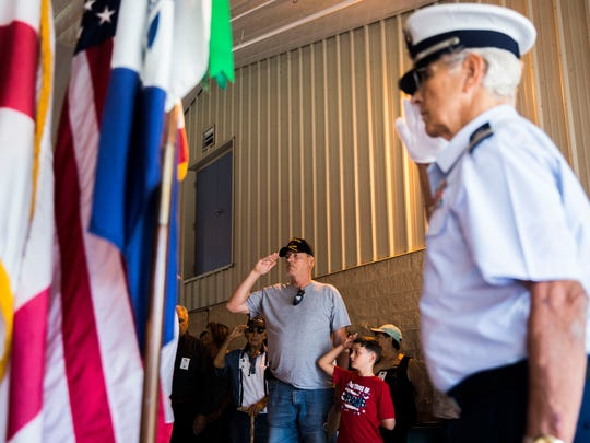 Steven Smith, 58, left, and his grandson, Steven Schindler, 11, right, salute during the pledge of allegiance during the Memorial Day Ceremony at Veterans Memorial Elementary School on Thursday, May 24, 2018.