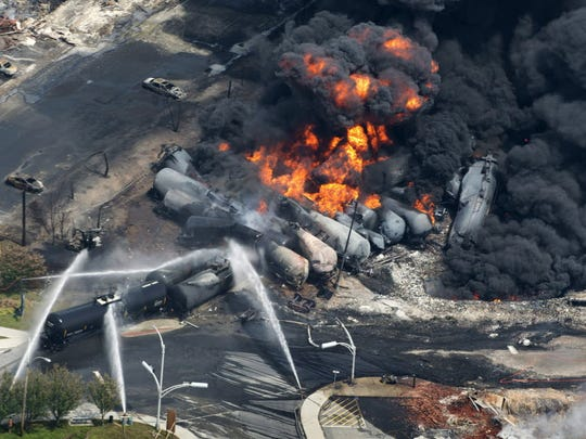 In a July 6, 2013, photo, smoke rises from railway cars that were carrying crude oil after derailing in downtown Lac Mégantic, Quebec, Canada.