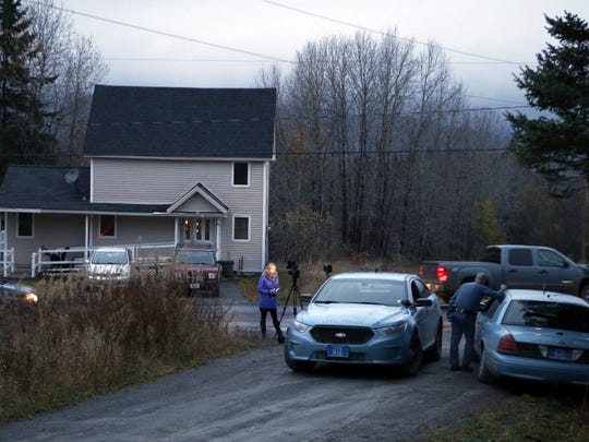 10/29/14 - State troopers and a television reporter stand across from the home where Kaci Hickox, a nurse who treated Ebola patients in West Africa, is staying, Wednesday, Oct. 29, 2014, in Fort Kent, Maine. Hickox said Wednesday she plans to stop quarantining herself in rural Maine, signaling a potential showdown with state police monitoring her home and state officials preparing to legally enforce the quarantine. She said she'll defy the state if the policy isn't changed by Thursday.