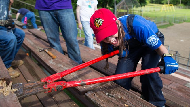 Abbi Klopp cuts bolts from rotting wood on the bleachers at Albion's Harris Field as part of the Knox Presbyterian Church service project.