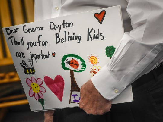 Gov. Mark Dayton holds signs created by students and given to him by Talahi Community School students Thursday, May 10, in St. Cloud.