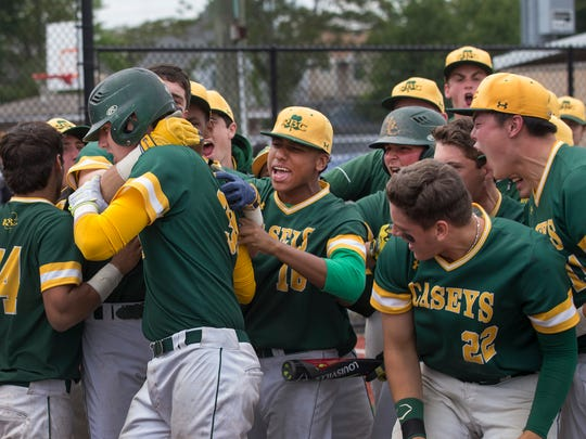Red Bank Catholic's Brian Sheehy is mobbed by team mates hitting a home run  driving in two runs to defeat Manchester in Shore Conference play 2-1.