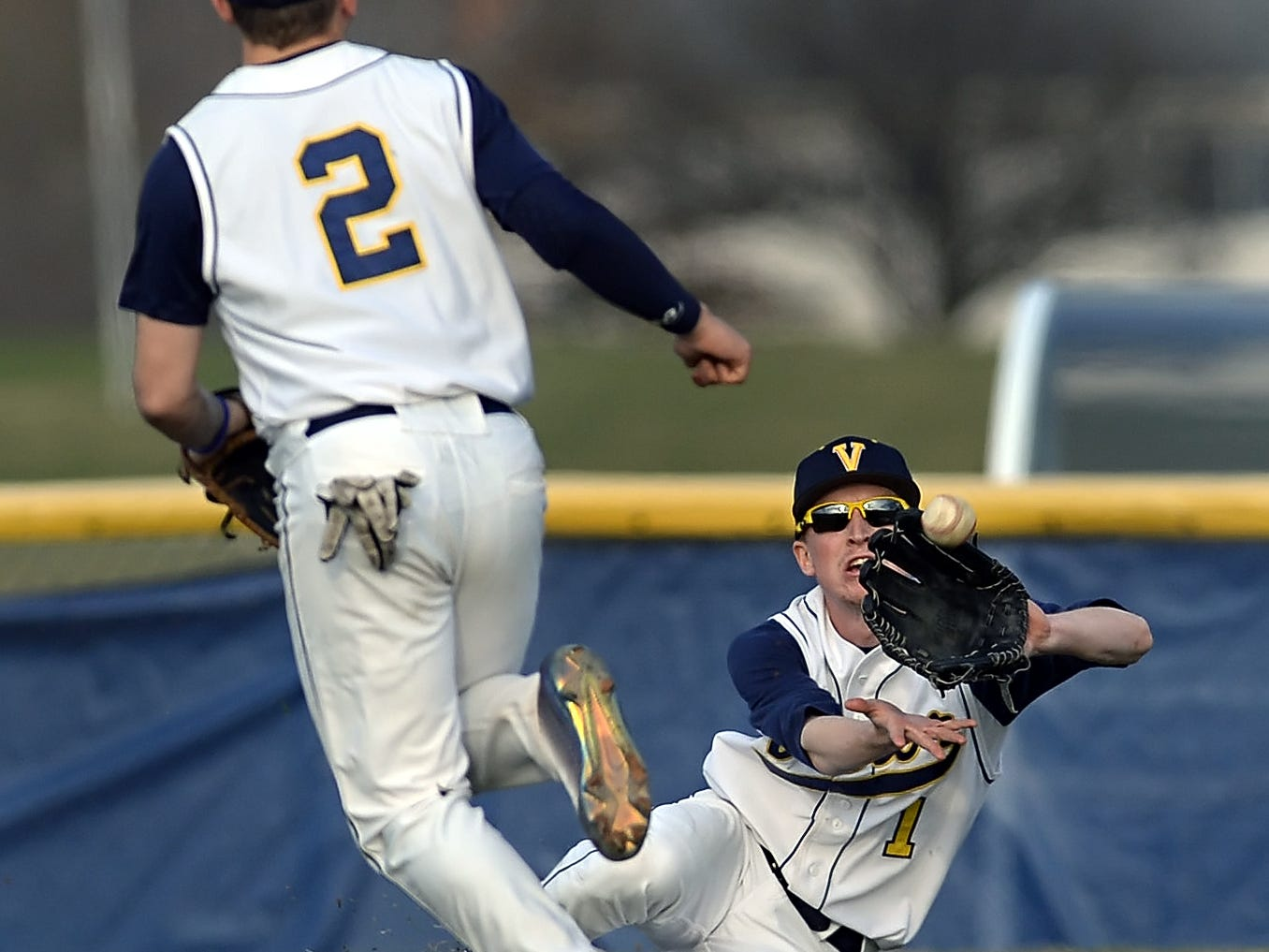Victor's Chad Messier, right, makes a sliding catch in right field in front of teammate Ben Banaszak during a regular season game played at Victor High School on Monday, April 13, 2015. Brockport beat Victor 5-3.