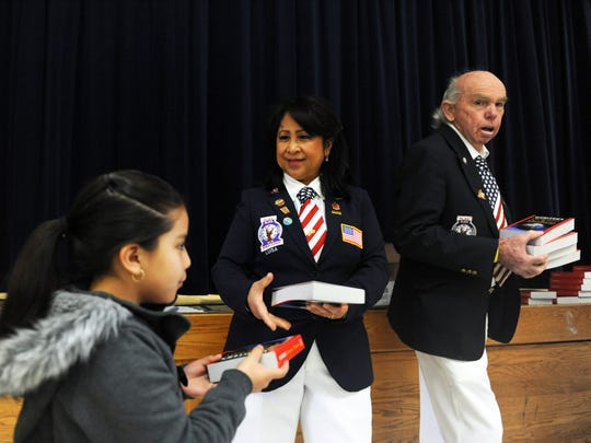 From right, Lawrence Mosher and Gli M. VonWinning of local Elks Lodge No. 614 pass out new dictionaries to 3rd-graders at New Republic Elementary School in Salinas.