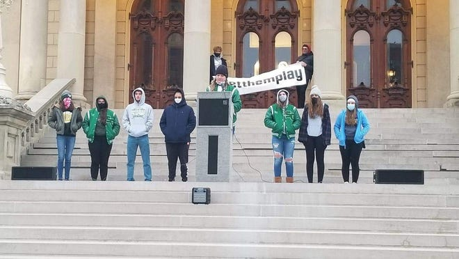 Sand Creek's Kendall Covey speaks at the podium in Lansing at the #LetThemPlay rally in front of group of Sand Creek students.
