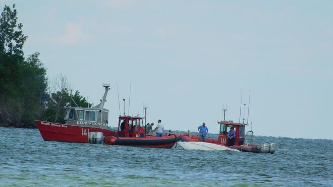 Recovery teams assess the situation when a boat sank in Lake Erie in Bolles Harbor Sunday.