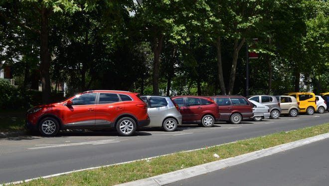 Line of parked cars on the street in residential area of an European city