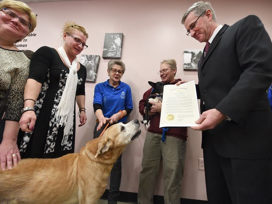 Pennsylvania Agriculture Secretary Russell C. Redding, right, presents a proclamation from Gov. Tom Wolf naming March Dog License Awareness Month, as Dawson the dog barks.