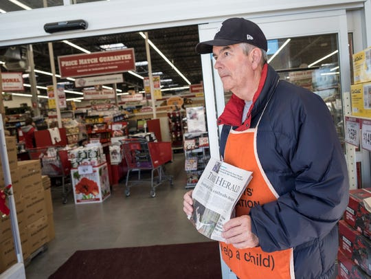 Ron Young sells copies of the Times Herald in the entry