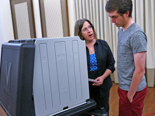 First-time voter Carson Jones, right, gets instructions on the voting booth from precinct judge Laurie Gavrin before casting his ballot.