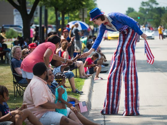 Aubrey Meade of Lincoln Park high-fives a child while stilt walking in the annual Independence Day Parade in Oak Park on Wednesday, July 4, 2018.