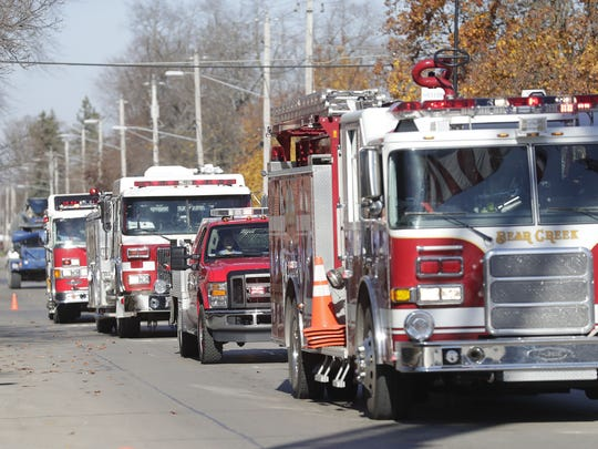 Fire equipment from multiple departments form a procession