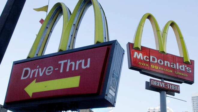 FILE - In this Dec. 20, 2010, file photo, McDonald's signs sprout from the restaurant's parking lot in New York. The Chicago Tribune reported on May 27, 2016, that a blind Louisiana man is suing the chain over its refusal to serve customers at drive-thru windows who aren't in vehicles. (AP Photo/Richard Drew, File)