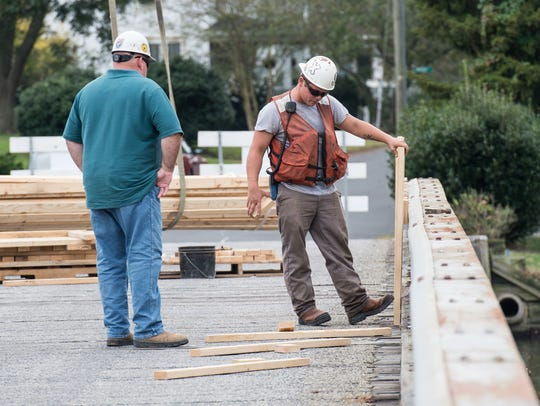 Construction workers place materials on the Mount Prospect