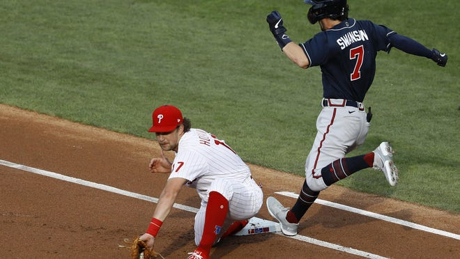 Philadelphia's Rhys Hoskins fields a throw for an out against Atlanta's Dansby Swanson on Saturday.