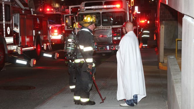 Firefighters talk with residents after a small fire hit an apartment building on Pleasant Street early Monday.