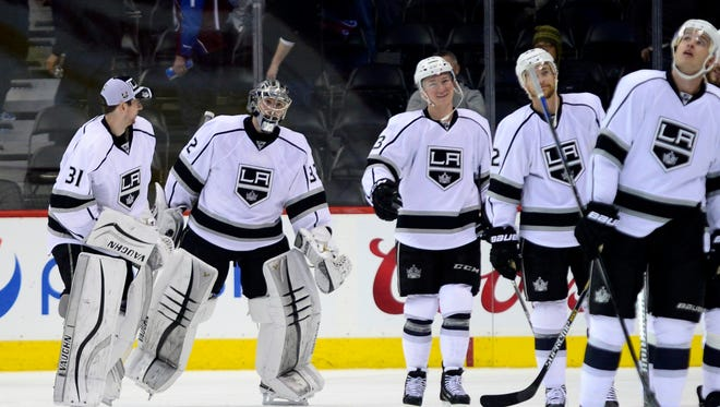 Los Angeles Kings goalie Jonathan Quick (32) (center) celebrates the win with goalie Martin Jones (31) against the Colorado Avalanche at the Pepsi Center.