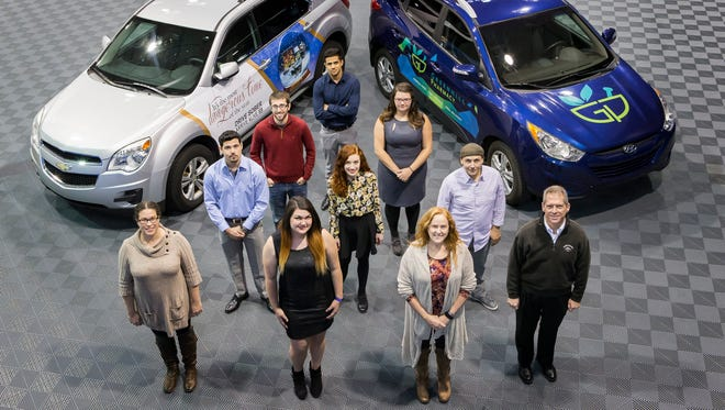 Carvertise employees pose for a portrait with two cars wrapped in advertisements at the company's workshop in New Castle on Thursday afternoon.