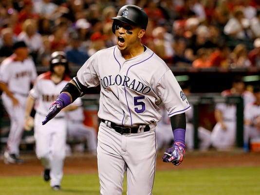 Colorado Rockies right fielder Carlos Gonzalez (5) crosses the plate after hitting a solo home run against the Arizona Diamondbacks during the third inning of a baseball game, Monday, April 4, 2016, in Phoenix. (AP Photo/Matt York)