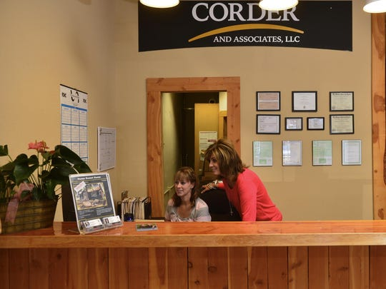 Staci Corder, who co-owns Corder and Associates with her husband Trampus, talks with their office manager April Smith.