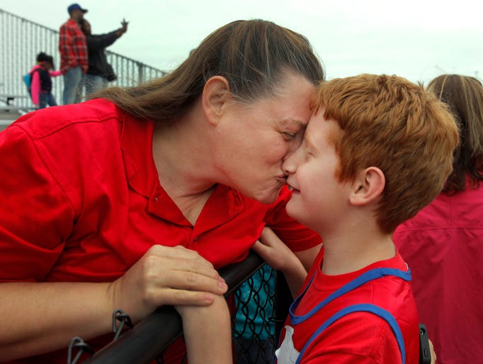 Candi Jones, left, kisses her son Alistair Jones, right, 10, after he finished first in his heat of the 50 meter run at the Special Olympics held at Greece Arcadia HS on Wednesday.