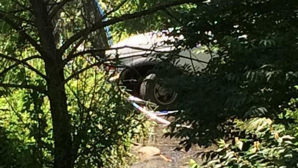 A trampoline is pinned under the front of a truck that crashed through a backyard, killing one child and injuring a second, before coming to rest in a water-filled ditch.