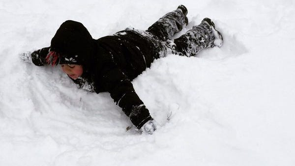 Jace Rouse, 4, makes a snow angel. He loves the snow even if it's cold.