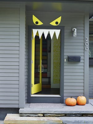 Quickly make an amusing Halloween front door with craft foam: Using removable foam-mounting squares, attach pointy white teeth so they hang from inside the door frame and two large, yellow eyes with black pupils mounted above the doorway.