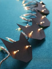 Transform a string of orange lights into black cats, using a FamilyFun magazine template (familyfunmag.com/printables). String them on the front door or in a child's room.