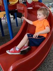 Cameron Pierce goes down a playground slide at the