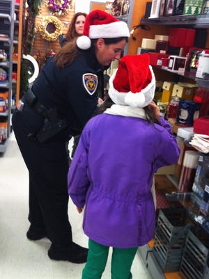 Fairfield Township Police Officer Jill Ebbing helps a child select an item during last year's Shop With A Cop program. Ebbing is participating in this year's event Saturday, at the Bridgewater Falls shopping center.