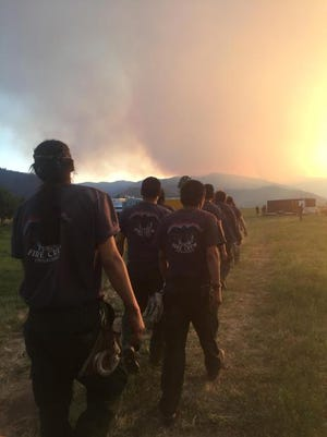 Firefighters from the Yukon trudge off to dinner after a long day fighting western Montana's Sunrise fire.