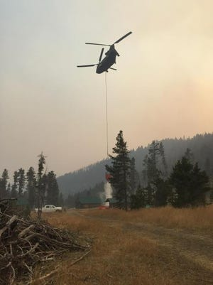 A helicopter drops water on a hot spot on the Alice Creek fire Friday.