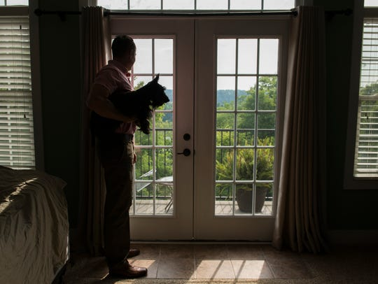 Rob Niemann looks outside his home with his dog, Maria.