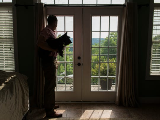 Rob Niemann looks outside his home with his dog, Maria. Niemann has space in his home ready to rent on Airbnb for the eclipse in August.