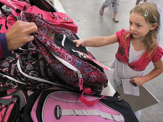 Bella Kirby receives a free backpack during the 2013 Tools for School school supply giveaway at the Delaware County Fairgrounds. Hearts & Hands United is beginning its fundraising efforts for its annual giveaways of school supplies and coats to help families in need.