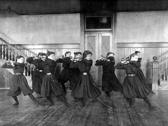Girls work out with dumbells in a high school gym class in 1899.