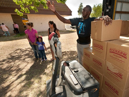 Bernard Lang calls for a dolly to load boxes of food at the Lindsay Community Center on June 12.