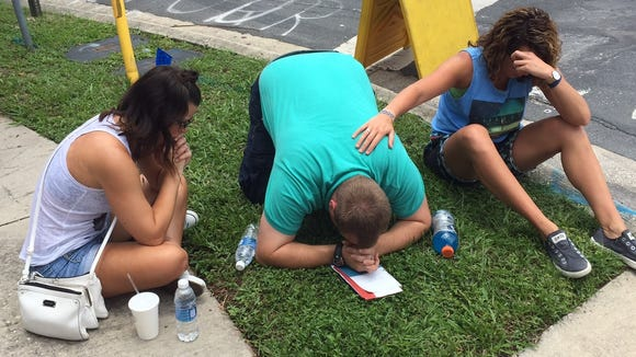 People pray near the scene of a shooting that left